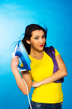 Houseworks, woman with pile of clothes for ironing, on blue background photo