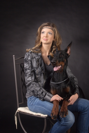 Woman with dobermann dog on black background photo