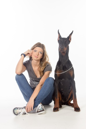 Young woman with black dobermann dog, isolated on white photo