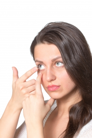 Young woman inserting contact lenses to eye