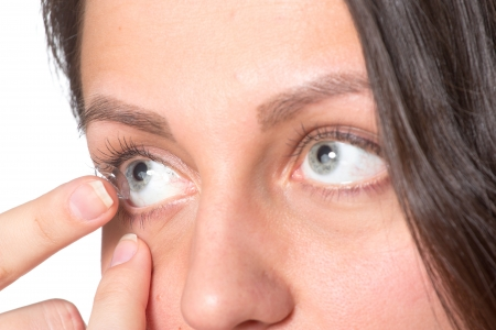 insertion: Young woman inserting contact lenses to eye