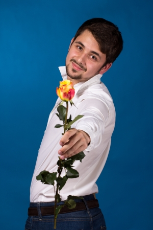 young man giving a red rose, on blue background