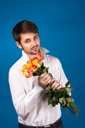 celebration smiley: young man giving a red rose, on blue background