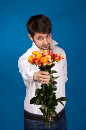suprise: young man giving a red rose, on blue background