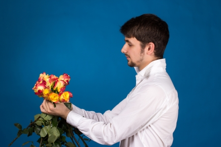 celebration smiley: Man with bouquet of red roses. On blue background.
