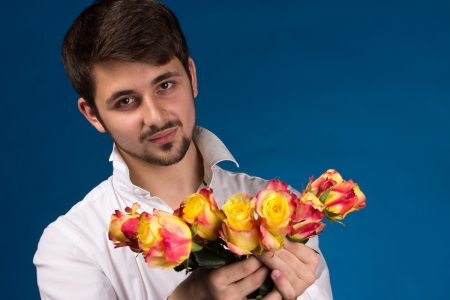 suprise: Man with bouquet of red roses. On blue background.