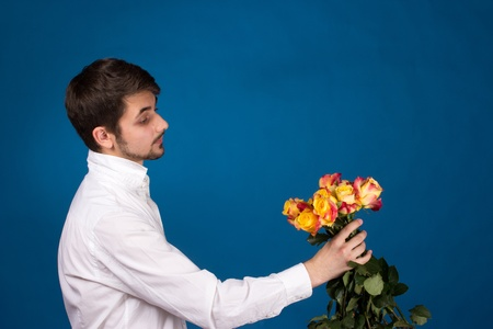 Man with bouquet of red roses. On blue background.