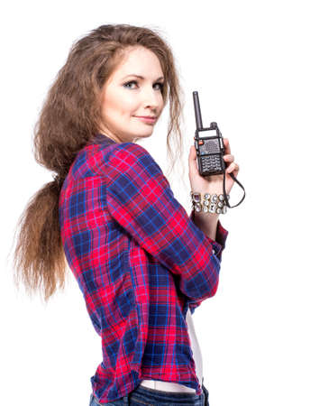 Attractive young woman in a checkered shirt with walkie talkie, isolated photo