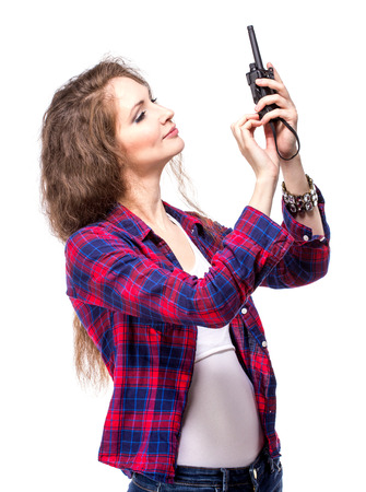 Attractive young woman in a checkered shirt with walkie talkie, isolated