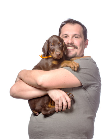 Young man is holding his sweet doberman puppy isolated on white  photo