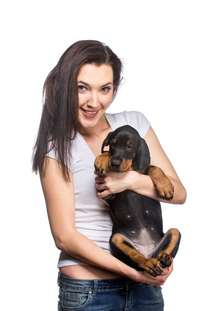 Brunette girl with her doberman puppy isolated on white background photo