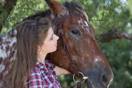 caresses: Young woman with horse, close up portrait