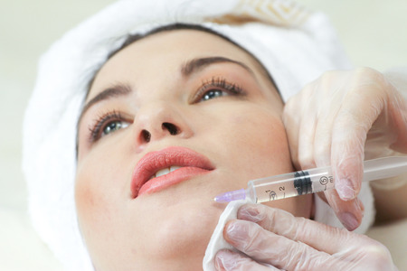 augmentation: Woman Having Botox Treatment At Beauty Clinic, close up. Focus on syringe