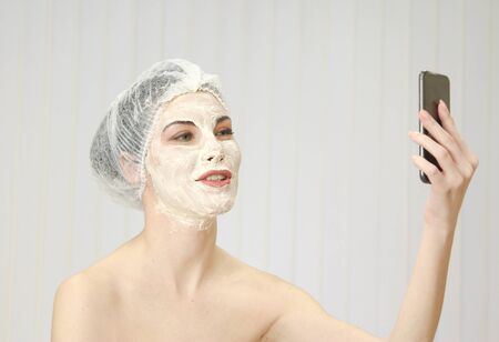 nourishing: Relaxed woman with a deep cleansing nourishing face mask applied to her face, beauty and skincare concept