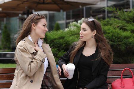 Girlfriends having fun on bench outdoors daytime