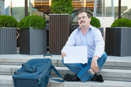 Sad man sitting on the steps with a suitcase Empty sign outdoors