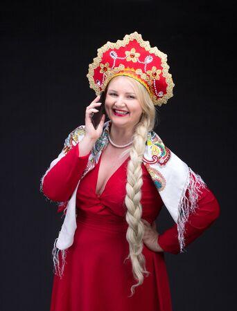kokoshnik: Girl standing in Russian traditional dress. Do selfie. Woman is wearing sarafan and kokoshnik. The girl in red old russian dress. Isolated on black. Stock Photo