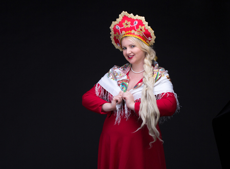 kokoshnik: Girl standing in Russian traditional costume. Plus size Woman is wearing sarafan and kokoshnik. The girl in red old russian dress. Isolated on black.