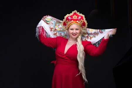 kokoshnik: Girl standing in Russian traditional costume. Woman is wearing sarafan and kokoshnik. The girl in red old russian dress. Isolated on black.