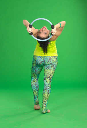 magick: Woman doing pilates with ring on green background Stock Photo