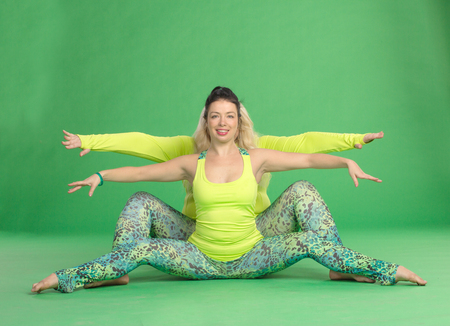 legs wide open: Two girlfriends doing stretching exercise tilts to the side together sitting on the floor on green background