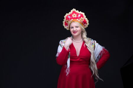 kokoshnik: Girl standing in Russian traditional costume. Plus size Woman is wearing sarafan and kokoshnik. The girl in red old russian dress. Isolated on black.