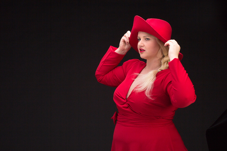 Sexy plus size woman in red hat with red lips looking at camera. Isolated on black. Banco de Imagens