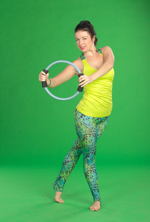 saxy: Woman doing pilates with ring on green background Stock Photo