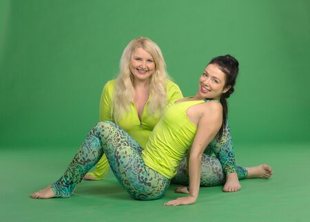 closed club: Plus size and slim girls making yoga poses on green background