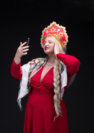 kokoshnik: Girl standing in Russian traditional costume. Do selfie. Woman is wearing sarafan and kokoshnik. The girl in red old russian dress. Isolated on black. Stock Photo