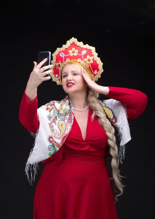 kokoshnik: Girl standing in Russian traditional costume. Do selfie. Woman is wearing sarafan and kokoshnik. The girl in red old russian dress. Isolated on black. Stock Photo