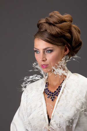 gr: Beautiful brown-haired woman with evening make-up, with amethyst necklace and scarf ostrich down on a gray background