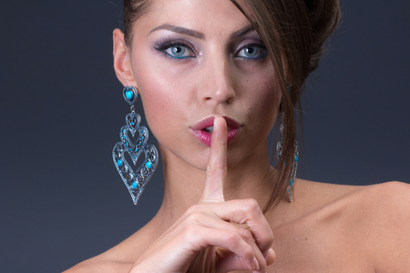 quarz: keep silence signal from beauty Woman wearing shiny earring Stock Photo