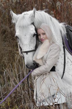 horse blonde: Blonde girl with white horse on sundown Stock Photo