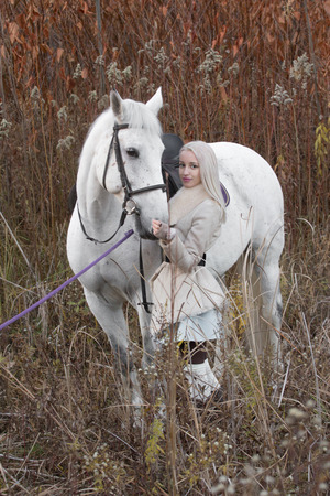 horse blonde: Two blonde, girl with a horse on field Stock Photo