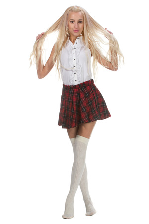 Young and beautiful schoolgirl is wearing a traditional uniform is smiling on white background. Senior high school student in uniform hold long hair in hands.