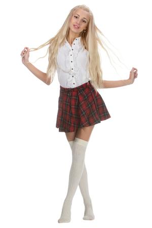 faldas: Colegiala joven y bella es que llevaba un uniforme tradicional est� sonriendo en el fondo blanco. Estudiante de bachillerato en uniforme mantener el pelo largo en las manos.