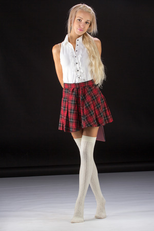 Lovely sexy blonde girl in plaid short skirt, isolated on white