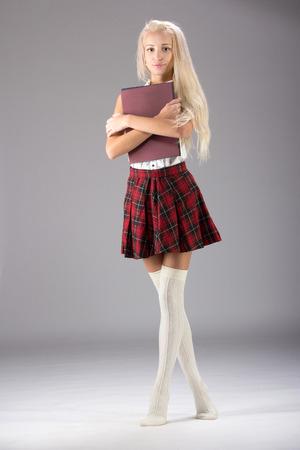 falda corta: Encantadora chica sexy rubia en falda corta a cuadros, aislado en blanco Foto de archivo