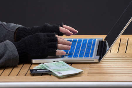 stolen: Hackers hands on keybord with stolen money and credit card Stock Photo