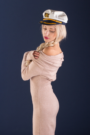 madam: Sexy blonde with long hair in a beautiful dress and captains cap Stock Photo