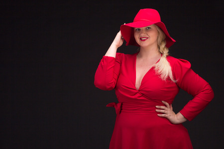 Sexy plus size woman in red hat with red lips looking at camera. Isolated on black. Banque d'images