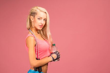sexy blonde girl: Portrait of young and healthy blonde with skipping rope and bottle of water over the pink background
