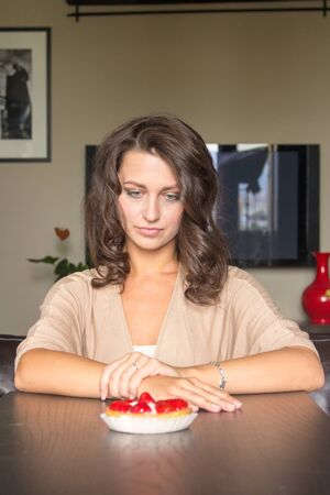 guilty pleasures: Pretty girl Looking to strawberry cake in living room