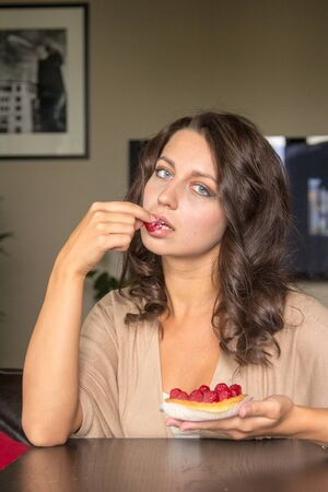 guilty pleasure: Young grey eyes woman eats the  raspberry cake at the table in living room