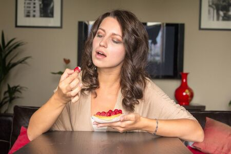 guilty pleasures: Young grey eyes woman eats the  raspberry cake at the table in living room