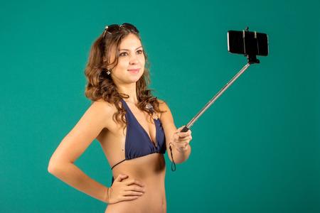 traje de bano: Feliz mujer joven en traje de ba�o azul bikini tomando autofoto con smatphone sobre fondo verde