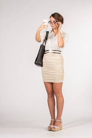 secretary skirt: Secretary girl in a short beige skirt with sunglasses, bag and mobile phone. Using mobile phone as mirror. Stock Photo