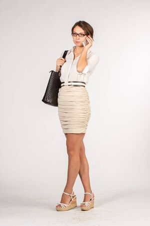 secretary skirt: Secretary girl in a short beige skirt with sunglasses, bag and mobile phone. Mobile phone speaking.