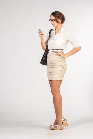 falda corta: Chica Secretario en una falda color beige corto con gafas de sol, bolso y tel�fono m�vil Foto de archivo